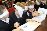 Akcijos KNYGŲ KALĖDOS metu vaikai užrištomis akimis skaitė knygas